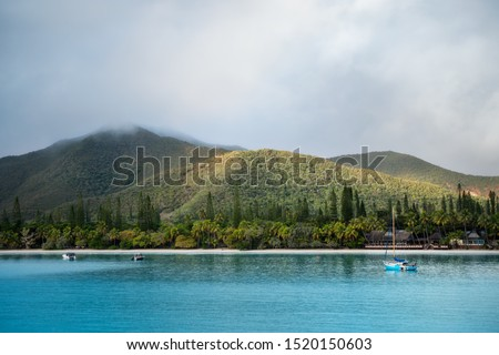 Kuto Bay View with turquoise waters, a white sandy beach, a waterfront restaurant and Pic N'Ga Mountain top engulfed in clouds and sun lit mountain ridges on the secluded Isle of Pines, New Caledonia.