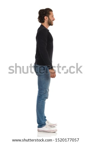 Handsome young man in jeans, sneakers and black jersey is standing relaxed, looking away and smiling. Full length studio shot isolated on white. #1520177057
