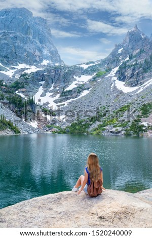 Young woman enjoying time by lake on  hiking trip in beautiful mountains. Early summer landscape with  snow covered mountains.  Emerald Lake. Estes Park. Rocky Mountains National Park, Colorado, USA #1520240009