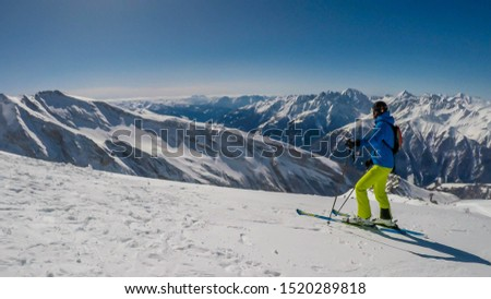 A skier going down the slope in Heiligenblut, Austria. Perfectly groomed slopes. High mountains surrounding the man wearing yellow trousers and blue jacket. Man wears helm for the protection. #1520289818