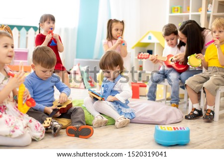 Kindergarten teacher with children on music lesson in day care. Little kids toddlers play together with developmental toys. #1520319041