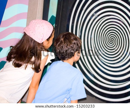 Sister and brother observing the optical illusion swirl at the science centre