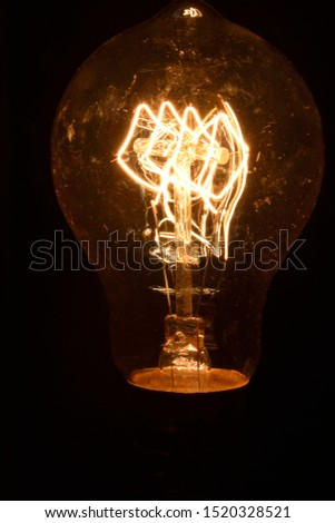 A vertical light bulb turned on against the dark background illuminating and exposing the lighting element #1520328521