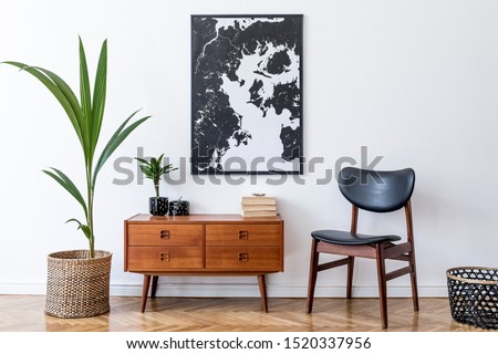 Stylish interior design of living room with wooden retro commode, chair, tropical plant in rattan pot, basket and elegant personal accessories. Mock up poster frame on the wall. Template. Home decor. #1520337956