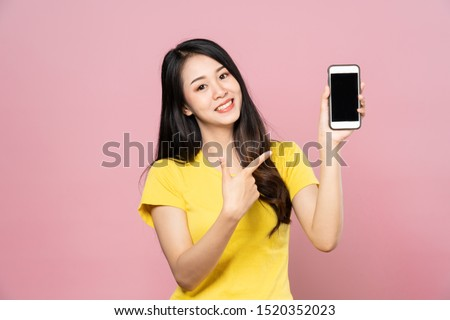 Portrait of Asian beautiful young woman holding smartphone and pointing finger on mobile phone with smile face. The girl standing and looking at camera in studio. Advertisement & presentation concept. #1520352023