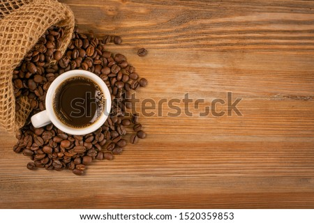 Hot coffee cup and coffee beans on brown wooden table background top view with copy space. White coffeecup or mug with black beverage topview with place for text #1520359853