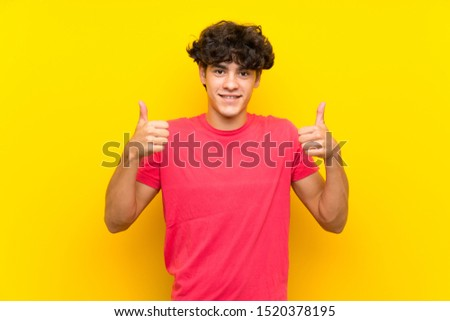Young man over isolated yellow wall giving a thumbs up gesture #1520378195