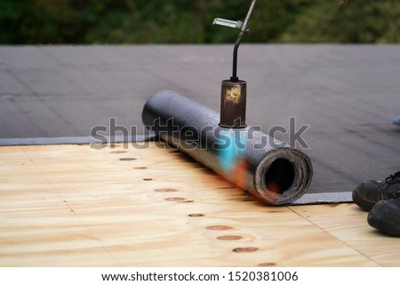 Bitumen roofing.  A with a gas burner and a roll of tar paper. Flat roof installation. Royalty-Free Stock Photo #1520381006