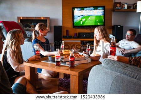 Lublin / Poland - May 12, 2018: Friends enjoying watching football game on TV drinking cold drinks and eating snacks talking and spending time together. Real people, authentic situations #1520433986