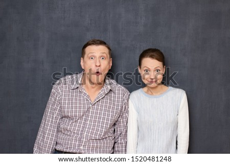 Studio half-length portrait of funny caucasian young adult couple grimacing and making foolish surprised faces with absurd expression, fooling and having fun together, standing over gray background #1520481248