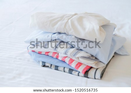 Hotel room with freshly made bed, perfectly clean and ironed sheets, stack of new dry cleaned folded set of clothing in natural sun light. Close up, copy space for text. #1520516735
