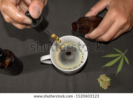 Pouring CBD tincture in a coffee cup, natural remedy of marihuana. Person using cannabis oil with a dropper in a table with marihuana leaf. Royalty-Free Stock Photo #1520603123