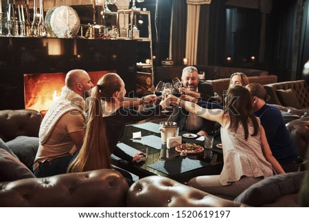 Knocking glasses. Family friends have nice evening near the fireplace in luxury modern restaurant. Royalty-Free Stock Photo #1520619197