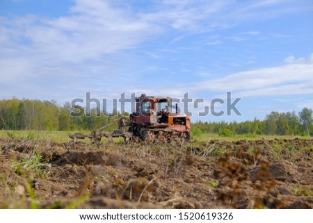 A tracked tractor with a plough plows the ground in autumn against the background of the forest. #1520619326