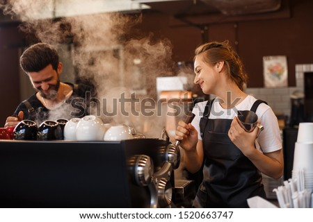 Two young smiling barista at work. Professional barista team brewing coffee using coffee machine in coffee shop. Happy young man and woman developing own coffee business.  #1520663747
