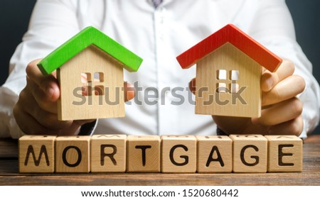 Wooden blocks with the word Mortgage and businessman. The concept of buying a home on credit. Loan for apartments and housing. Interest rates. Creditor, debtor. Real estate #1520680442