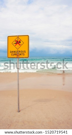 Danger Current Sign next to a blue turquoise ocean. Good day for Beach #1520719541
