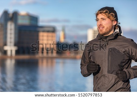 Winter running athlete man jogging outdoor in city outside wearing cold weather accessories - hat ,gloves , windproof sport jacket. Active healthy lifestyle. Royalty-Free Stock Photo #1520797853