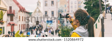 Quebec city old town tourist taking picture with mobile phone of Place Royale panoramic banner. Asian chinese woman on Autumn Canada travel.