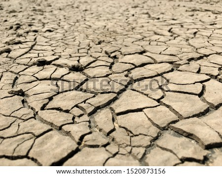 Closeup weathered texture and background of arid cracked ground. Broken dried mud from arid problem. Global warming crisis. Agricultural land without water. Climate change Royalty-Free Stock Photo #1520873156