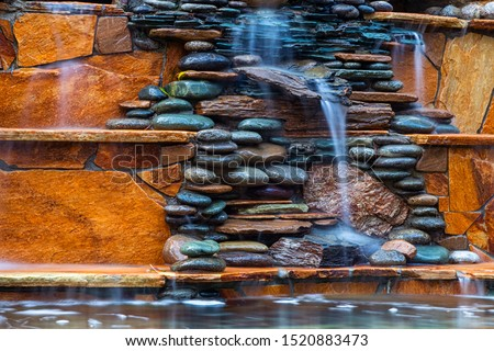 Larger plan A beautiful fountain, made of different stones, water flows from several clay jugs into a large pool with clear water. Pacifying picture of running water