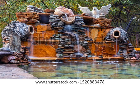 A beautiful fountain, made of different stones, water flows from several clay jugs into a large pool with clear water. At the fountain sits  white statue of an owl. Pacifying picture of running water
