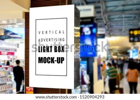 Mock up blank vertical light box with clipping path placed near entrance and walkway in shopping centre, empty space for advertising or information, advertising concept