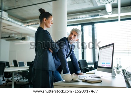 Two businesspeople with computer standing in an office at desk, working. #1520917469