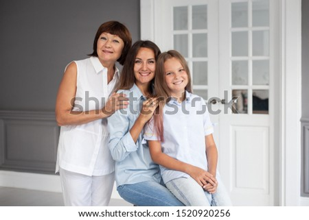 Daughter, mother and grandmother stand closeto each other and hugging #1520920256
