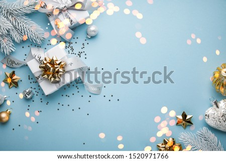 Merry Christmas and Happy Holidays greeting card, frame, banner. New Year. Noel. Christmas white, silver and golden ornaments and gift on blue background top view. Winter xmas holiday theme. Flat lay #1520971766