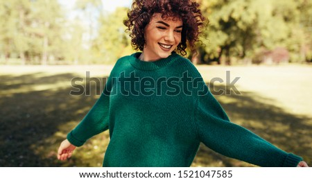 Horizontal image of beautiful young woman smiling posing against nature background with windy curly hair, have positive expression, wearing in green sweater. People, travel and lifestyle concept.  #1521047585