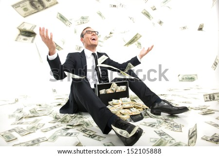 I am rich! Happy young businessman in formalwear throwing money up while sitting near the case full of paper currency Royalty-Free Stock Photo #152105888