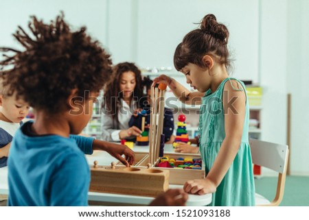 Adorable little children and their teacher playing with toys at kindergarten #1521093188