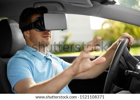 virtual reality, technology and driving concept - man or driver wearing vr glasses in car #1521108371