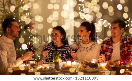 holidays and celebration concept - happy friends having christmas dinner at home and drinking red wine #1521110393