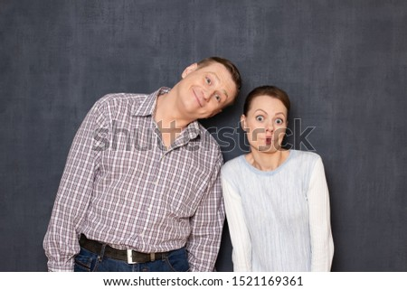 Studio waist-up portrait of funny caucasian young adult couple, man is kindly smiling, woman is making foolish surprised stupid face, both are fooling and having fun together, over gray background #1521169361