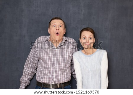 Studio waist-up portrait of funny caucasian young adult couple grimacing and making foolish surprised faces with awkward expression, fooling around, having fun together, standing over gray background #1521169370