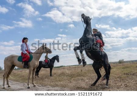 Slavuta, Ukraine - september 22, 2019 : Ukrainian men on horseback participate in the Ethno-eco festival Kolodar in city Slavuta, Ukraine #1521191672