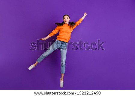 Full size photo of positive cheerful teen girl hold hand jump catch her flying parasol on windy weather wear orange sporty outfit jeans white sneakers isolated over violet purple color background #1521212450