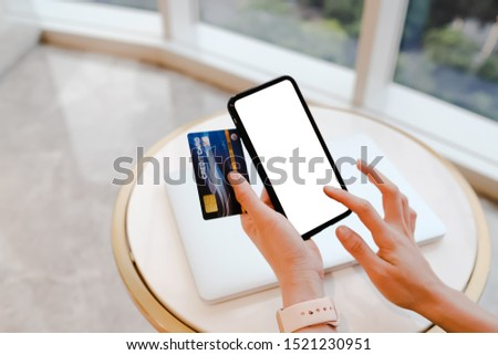 Close up of woman using blank cell phone and credit card sending massages shopping online on the coffee shop.