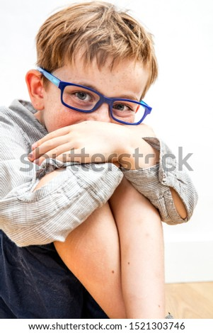 beautiful joyful child with eyeglasses hiding his giggle in his knees and hands for happiness, shyness, humour, wellbeing and joy of childhood #1521303746