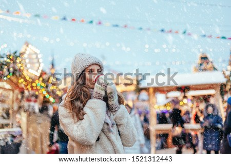 Girl drinking hot coffee while walking in Christmas market decorated with holiday lights in the evening. Feeling happy in big city. Spending winter vacations in Red square, Moscow, Russia. #1521312443