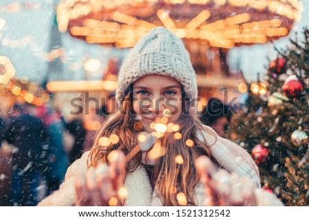 Girl walking in Christmas market decorated with holiday lights in the evening. Feeling happy in big city. Spending winter vacations in Red square, Moscow, Russia. #1521312542