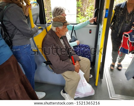 Craiova, Dolj/Romania - October 03, 2019 old and poor man, with dirty clothes going by bus full of people #1521365216