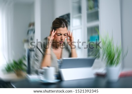 Sick dizzy young woman suffering headache while working on her laptop at home. Covid-19 woman on quarentine doing tele work and suffering symptoms. #1521392345