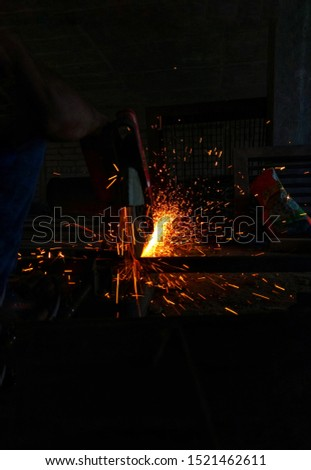 cutting of iron steel angle bars with motorised steel cutter grinder machine and generation of sparks.