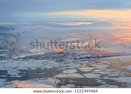 Aerial view of the small Arctic city of Anadyr, located on the coast of the Anadyr Estuary, surrounded by a vast tundra. November. Harsh cold climate in the far North of Russia. Chukotka, Siberia. #1521499484