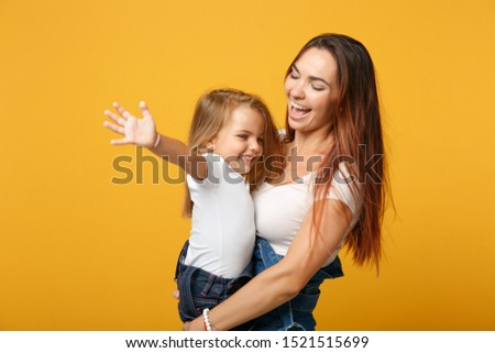 Woman in light clothes have fun with cute child baby girl 4-5 years old. Mommy little kid daughter isolated on yellow background studio portrait. Mother's Day love family parenthood childhood concept #1521515699