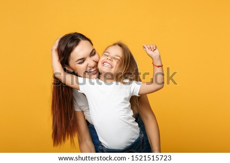 Woman in light clothes have fun with cute child baby girl 4-5 years old. Mommy little kid daughter isolated on yellow background studio portrait. Mother's Day love family parenthood childhood concept #1521515723