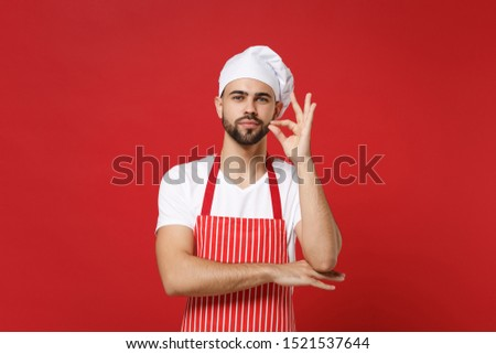 Young bearded male chef cook or baker man in striped apron white t-shirt toque chefs hat posing isolated on red background. Cooking food concept. Mock up copy space. Making okay taste delight sign #1521537644